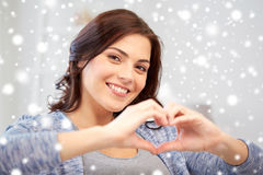 Happy young woman showing heart with hands at home Royalty Free Stock Photos