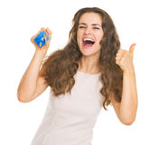 Happy young woman showing keys and thumbs up Stock Photography