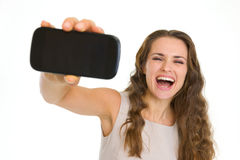 Happy young woman showing mobile phone Stock Images