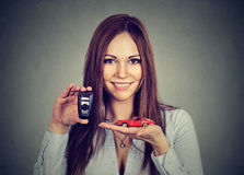 Happy young woman showing model car and remote keys Royalty Free Stock Image