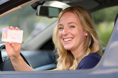 Happy young woman showing off her drivers license. Happy young blond woman sitting behind the steering wheel of a car showing off her drivers license through the royalty free stock images