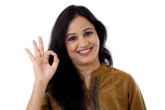 Happy young woman showing OK gesture against a white Royalty Free Stock Photography