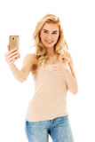 Happy young woman showing ok sing and taking pictures of herself at smart phone Royalty Free Stock Image