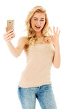 Happy young woman showing perfect sing and taking pictures of herself at smart phone Royalty Free Stock Photography