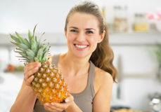 Happy young woman showing pineapple Royalty Free Stock Photography