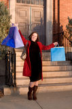 Happy young woman showing shopping bags. Happy, smiling young woman showing shopping bags, outside store Royalty Free Stock Photo
