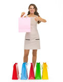Happy young woman showing shopping bags and thumbs up Stock Images