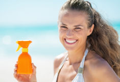 Happy young woman showing sun block creme Royalty Free Stock Photos