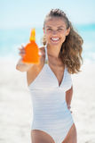 Happy young woman showing sun screen creme Stock Photo