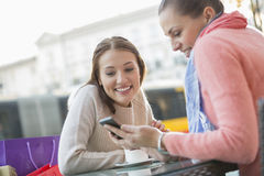 Happy young woman showing text message to friend at sidewalk cafe Stock Photos