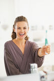 Happy young woman showing toothbrush Royalty Free Stock Images