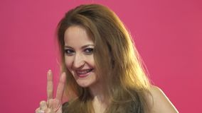 Happy young woman showing victory sign on pink background.  stock video footage