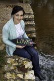 Happy young woman showing the words, Love, on a stone royalty free stock photo