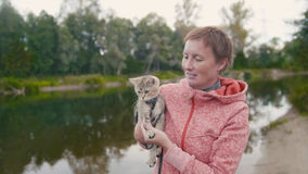 Happy young Woman shows the British Shorthair Tabby cat near forest river, outdoor Royalty Free Stock Photo