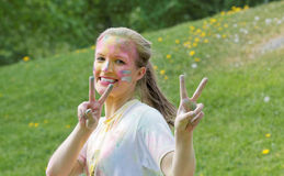 Happy young woman with silver color dust in her face making vict Royalty Free Stock Images