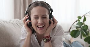 Happy woman listening to music on sofa at home stock video