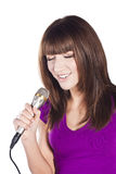 Happy young woman singing with microphone Stock Images
