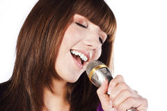 Happy young woman singing with microphone Stock Photo