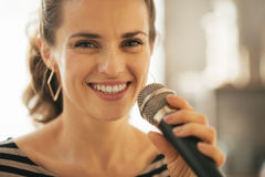 Happy young woman singing with microphone Royalty Free Stock Photography