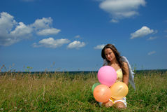 Happy young woman siting with colorful balloons Stock Photo