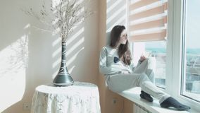 Happy young woman sits in the morning in the sun on a windowsill. A beautiful girl sits by the window in the sunshine. From the curtains. A girl in pajamas, a stock footage