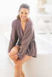 Happy young woman sitting on bathtub Royalty Free Stock Image