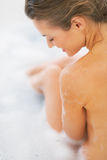 Happy young woman sitting in bathtub. rear view Royalty Free Stock Photography