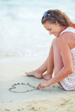 Happy young woman sitting on beach Stock Photography