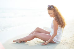 Happy young woman sitting on beach in the evening Royalty Free Stock Photo