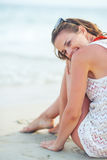 Happy young woman sitting on beach in the evening Royalty Free Stock Image