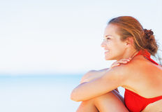 Happy young woman sitting on beach and looking on copy space Royalty Free Stock Photos