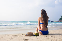 Happy young woman sitting on the beach with Stock Photo