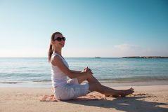 Happy young woman sitting on the beach Royalty Free Stock Photography