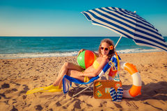 Happy young woman sitting on the beach Stock Photo