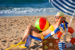 Happy young woman sitting on the beach Royalty Free Stock Photo