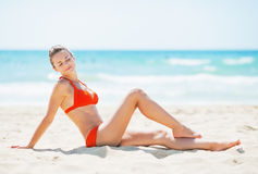 Happy young woman sitting on beach Royalty Free Stock Photography