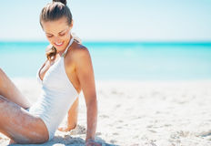 Happy young woman sitting on beach Royalty Free Stock Image