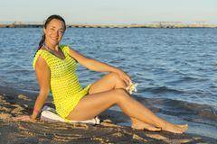Happy young woman sitting on beach. woman sitting on sandy beach against blue sky outdoors. An attractive young woman sits on a stock image