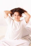 Happy young woman sitting in bed Royalty Free Stock Photo