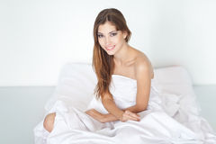 Happy young woman sitting on bed Royalty Free Stock Photography