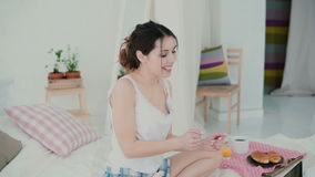 Happy young woman sitting on the bed and dancing. Brunette girl uses laptop, browses the Internet during breakfast. Royalty Free Stock Photography