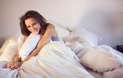 Happy Young Woman Sitting on Bed Looking Fresh. Cheerful young woman in her room sitting on top of bed smiling at you Stock Photography