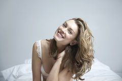 Happy Young Woman Sitting In Bed Stock Images