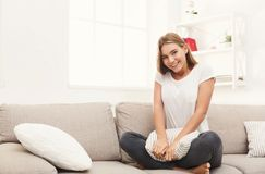 Young smiling woman sitting on beige couch Stock Photos