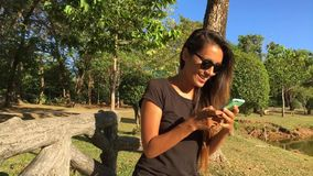 Happy Young Woman Sitting on the Bench in the Park and Typing Message on Smartphone. Slowmotion HD Steadicam Shot. stock video footage