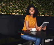 Happy young woman sitting in cafe holding digital tablet royalty free stock image