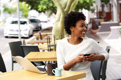 Happy young woman sitting at cafe with a mobile phone Royalty Free Stock Photography