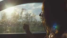 Happy young woman sitting in car passenger looking out window on sunny day enjoying rural car ride with lense flare Royalty Free Stock Photo