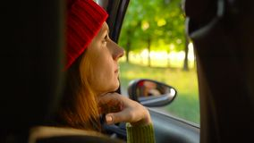 Happy young woman sitting in car passenger seat and looking out window on sunny day stock video footage