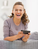 Happy young woman sitting on couch and writing sms Stock Photo